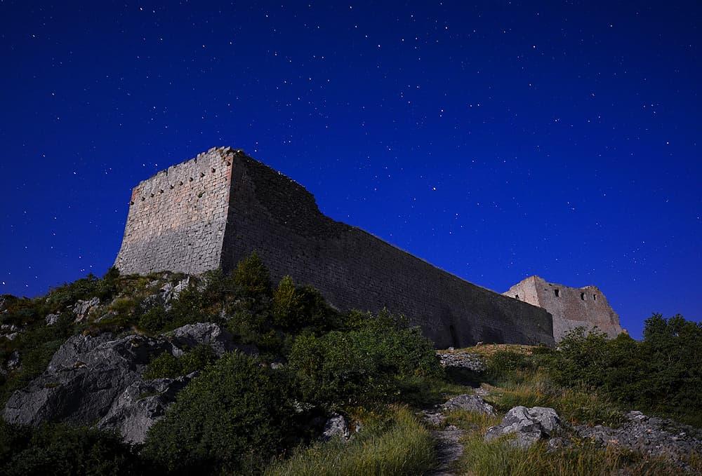 Le château de Montségur, un des derniers refuges des cathares en Ariège, sous le ciel étoilé, éclairé par la pleine lune (23 h 54)